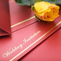a wedding invitation, with a yellow rose